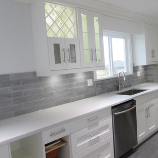 Inspiration for a mid-sized transitional galley separate kitchen in Vancouver with an undermount sink, shaker cabinets, white cabinets, solid surface benchtops, grey splashback, porcelain splashback, stainless steel appliances, porcelain floors, no island and grey floor.