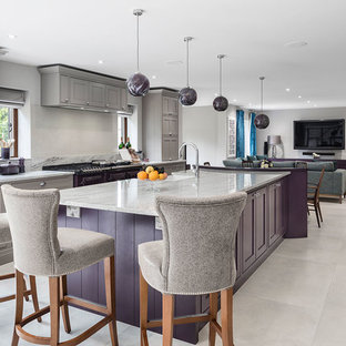 Expansive contemporary u-shaped open plan kitchen in Surrey with a farmhouse sink, shaker cabinets, purple cabinets, granite benchtops, beige splashback, glass sheet splashback, stainless steel appliances, ceramic floors, with island, grey floor and multi-coloured benchtop.