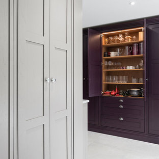 This is an example of an expansive country open plan kitchen in Surrey with a farmhouse sink, shaker cabinets, purple cabinets, granite benchtops, beige splashback, glass sheet splashback, stainless steel appliances, ceramic floors, with island, grey floor and multi-coloured benchtop.