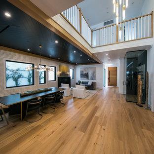 ロサンゼルスの中くらいのミッドセンチュリースタイルのおしゃれなキッチン (ダブルシンク、ガラス扉のキャビネット、白いキャビネット、クオーツストーンカウンター、ベージュキッチンパネル、シルバーの調理設備、淡色無垢フローリング、茶色い床、ベージュのキッチンカウンター) の写真