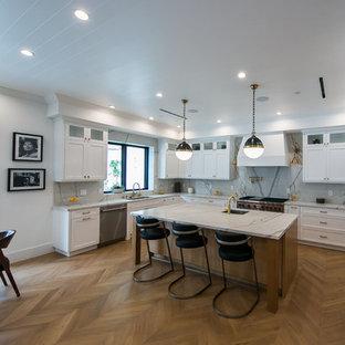 ロサンゼルスの中くらいのカントリー風おしゃれなキッチン (ダブルシンク、ガラス扉のキャビネット、白いキャビネット、クオーツストーンカウンター、ベージュキッチンパネル、シルバーの調理設備、淡色無垢フローリング、茶色い床、ベージュのキッチンカウンター) の写真