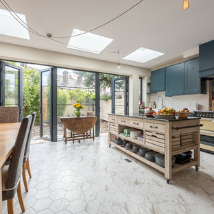 Design ideas for a mid-sized contemporary eat-in kitchen in London with a farmhouse sink, blue cabinets, multi-coloured splashback, ceramic splashback, marble floors, with island and multi-coloured floor.