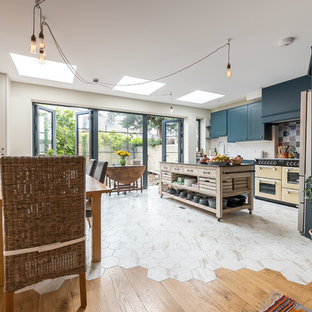 Medium sized contemporary l-shaped kitchen/diner in London with a belfast sink, blue cabinets, blue splashback, ceramic splashback, an island and multi-coloured floors.
