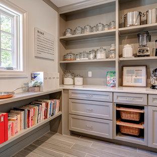 Modelo de cocina clásica renovada, grande, con despensa, armarios con paneles empotrados, puertas de armario grises, salpicadero verde y suelo de baldosas de porcelana