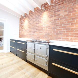 デヴォンの中サイズのコンテンポラリースタイルのおしゃれなキッチン (アンダーカウンターシンク、フラットパネル扉のキャビネット、グレーのキャビネット、人工大理石カウンター、マルチカラーのキッチンパネル、レンガのキッチンパネル、カラー調理設備、無垢フローリング、茶色い床) の写真