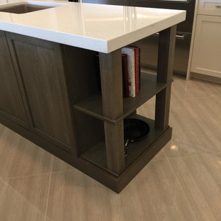 Design ideas for a mid-sized country l-shaped eat-in kitchen in Miami with an undermount sink, shaker cabinets, stainless steel appliances, with island, beige floor, granite benchtops, porcelain floors, beige cabinets, white splashback and mosaic tile splashback.