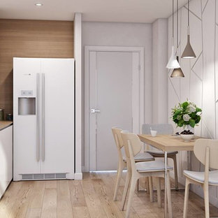 Mid-sized scandinavian eat-in kitchen designs - Inspiration for a mid-sized scandinavian l-shaped light wood floor and beige floor eat-in kitchen remodel in New York with a drop-in sink, flat-panel cabinets, white cabinets, wood countertops, brown backsplash, wood backsplash, white appliances, no island and brown countertops