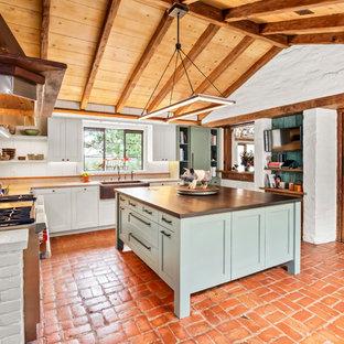 Exempel på ett stort amerikanskt grå grått kök, med en rustik diskho, luckor med infälld panel, blå skåp, träbänkskiva, rostfria vitvaror, tegelgolv, en köksö och vitt stänkskydd
