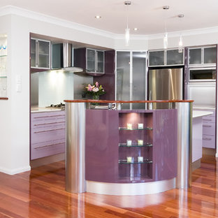 Contemporary kitchen ideas - Example of a trendy kitchen design in Brisbane with glass-front cabinets and stainless steel appliances