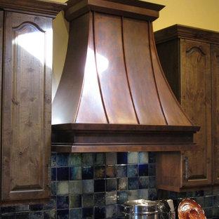 オースティンの中サイズのトラディショナルスタイルのおしゃれなキッチン (レイズドパネル扉のキャビネット、濃色木目調キャビネット、オニキスカウンター、青いキッチンパネル、磁器タイルのキッチンパネル、シルバーの調理設備の、セラミックタイルの床) の写真