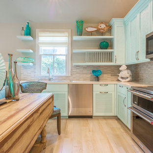 Cette photo montre une grande cuisine ouverte bord de mer en L avec un évier posé, un placard à porte persienne, des portes de placard bleues, une crédence grise, une crédence en carreau briquette, un électroménager en acier inoxydable, un sol en bois clair, un îlot central, un plan de travail en quartz modifié et un sol beige.