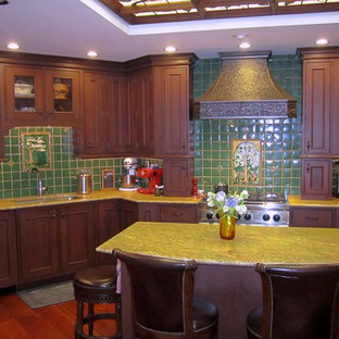 Photo of a large classic u-shaped kitchen/diner in Boston with a single-bowl sink, beaded cabinets, dark wood cabinets, marble worktops, green splashback, ceramic splashback, stainless steel appliances, dark hardwood flooring, an island, brown floors and yellow worktops.
