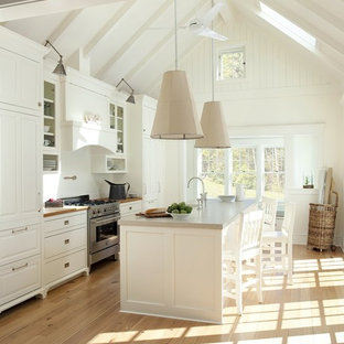 Inspiration for a beach style galley kitchen in Boston with raised-panel cabinets, white cabinets, concrete benchtops and white splashback.