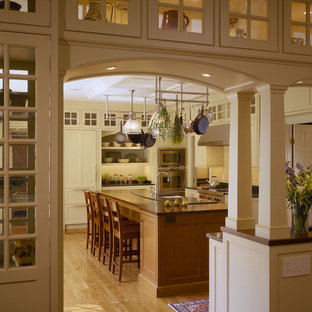 Inspiration for a mid-sized timeless u-shaped medium tone wood floor eat-in kitchen remodel in Boston with white cabinets, white backsplash, recessed-panel cabinets, solid surface countertops, stone tile backsplash, stainless steel appliances, an island and a farmhouse sink