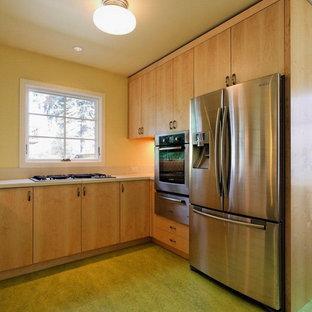 Aménagement d'une cuisine américaine classique en L avec un placard à porte plane, des portes de placard en bois clair, un plan de travail en béton et un sol vert.