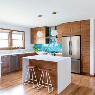 ポートランドの中サイズのミッドセンチュリースタイルのおしゃれなキッチン (アンダーカウンターシンク、フラットパネル扉のキャビネット、クオーツストーンカウンター、青いキッチンパネル、セラミックタイルのキッチンパネル、シルバーの調理設備の、無垢フローリング、中間色木目調キャビネット) の写真