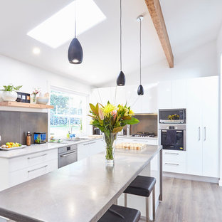 Inspiration for a contemporary l-shaped kitchen in Central Coast with a double-bowl sink, flat-panel cabinets, white cabinets, stainless steel benchtops, grey splashback, black appliances, light hardwood floors, with island, brown floor and grey benchtop.