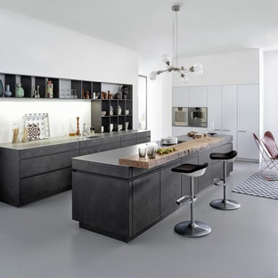 This is an example of a large rustic kitchen/diner in Boston with a submerged sink, flat-panel cabinets, distressed cabinets, concrete worktops, white splashback, integrated appliances and an island.