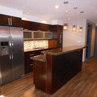 他の地域の中サイズのおしゃれなキッチン (ドロップインシンク、フラットパネル扉のキャビネット、濃色木目調キャビネット、コンクリートカウンター、グレーのキッチンパネル、ボーダータイルのキッチンパネル、シルバーの調理設備、無垢フローリング) の写真