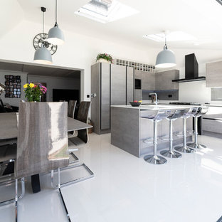 Inspiration for a medium sized industrial l-shaped kitchen/diner in London with a single-bowl sink, flat-panel cabinets, grey cabinets, quartz worktops, metro tiled splashback, black appliances, porcelain flooring, an island, white floors and yellow worktops.