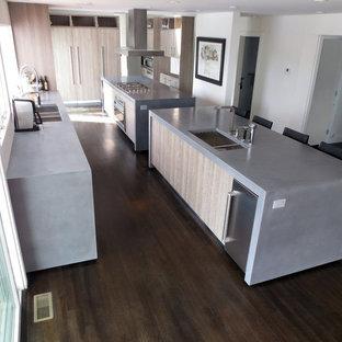 Esempio di una grande cucina abitabile minimal con top in cemento, 2 o più isole, lavello da incasso e parquet scuro