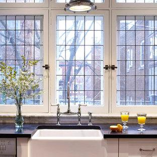 モントリオールの中サイズのインダストリアルスタイルのおしゃれなキッチン (エプロンフロントシンク、シェーカースタイル扉のキャビネット、白いキャビネット、クオーツストーンカウンター、白いキッチンパネル、サブウェイタイルのキッチンパネル、シルバーの調理設備の、無垢フローリング) の写真