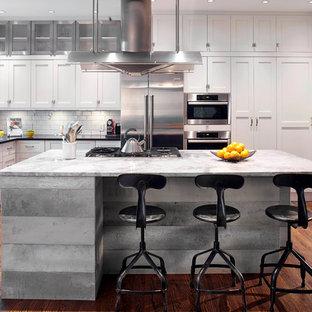 モントリオールの中サイズのインダストリアルスタイルのおしゃれなキッチン (エプロンフロントシンク、シェーカースタイル扉のキャビネット、白いキャビネット、御影石カウンター、白いキッチンパネル、サブウェイタイルのキッチンパネル、シルバーの調理設備の、無垢フローリング) の写真