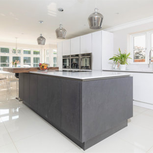 Large modern galley eat-in kitchen in Hampshire with an integrated sink, flat-panel cabinets, white cabinets, granite benchtops, white splashback, granite splashback, stainless steel appliances, ceramic floors, with island, beige floor and white benchtop.