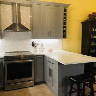 ボストンの小さいモダンスタイルのおしゃれなキッチン (シングルシンク、シェーカースタイル扉のキャビネット、グレーのキャビネット、大理石カウンター、白いキッチンパネル、サブウェイタイルのキッチンパネル、シルバーの調理設備の、セラミックタイルの床、ベージュの床、白いキッチンカウンター) の写真