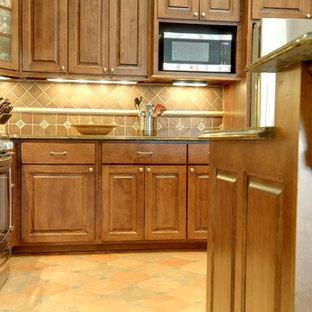 コロンバスの中サイズの地中海スタイルのおしゃれなキッチン (アンダーカウンターシンク、レイズドパネル扉のキャビネット、中間色木目調キャビネット、珪岩カウンター、茶色いキッチンパネル、テラコッタタイルのキッチンパネル、シルバーの調理設備の、リノリウムの床) の写真