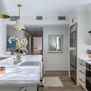 Transitional kitchen ideas - Transitional dark wood floor and brown floor kitchen photo in Miami with a farmhouse sink, beaded inset cabinets, white cabinets, white backsplash, stone slab backsplash, stainless steel appliances, an island and white countertops