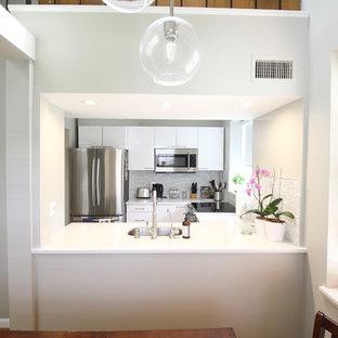 Свежая идея для дизайна: маленькая п-образная кухня в стиле модернизм с обеденным столом, врезной раковиной, плоскими фасадами, белыми фасадами, мраморной столешницей, серым фартуком, фартуком из стеклянной плитки, техникой из нержавеющей стали, полом из фанеры, островом и белой столешницей - отличное фото интерьера