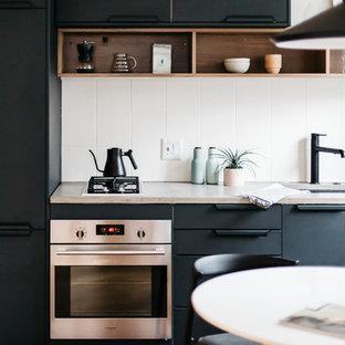 他の地域のモダンスタイルのおしゃれなII型キッチン (シングルシンク、フラットパネル扉のキャビネット、黒いキャビネット、コンクリートカウンター、白いキッチンパネル、シルバーの調理設備、無垢フローリング、グレーのキッチンカウンター) の写真