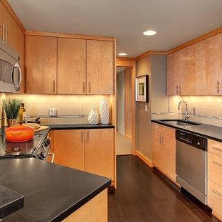 シアトルの小さいモダンスタイルのおしゃれなキッチン (フラットパネル扉のキャビネット、淡色木目調キャビネット、ベージュキッチンパネル、セラミックタイルのキッチンパネル、シルバーの調理設備の、濃色無垢フローリング、アイランドなし、アンダーカウンターシンク、ソープストーンカウンター、茶色い床) の写真