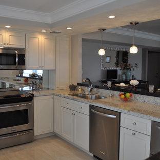Mittelgroße Klassische Wohnküche in U-Form mit Unterbauwaschbecken, Schrankfronten mit vertiefter Füllung, hellen Holzschränken, Granit-Arbeitsplatte, Küchenrückwand in Metallic, Rückwand aus Spiegelfliesen, weißen Elektrogeräten, Marmorboden und Halbinsel in Miami
