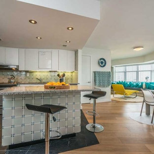 Small modern eat-in kitchen designs - Example of a small minimalist l-shaped slate floor eat-in kitchen design in Miami with flat-panel cabinets, white cabinets, quartz countertops, an island, a drop-in sink, gray backsplash, porcelain backsplash and stainless steel appliances