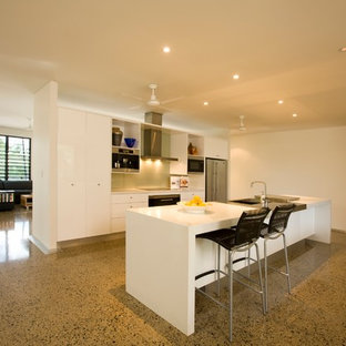 This is an example of a tropical galley open plan kitchen in Darwin with an integrated sink, flat-panel cabinets, white cabinets, solid surface benchtops, metallic splashback, glass sheet splashback, stainless steel appliances, concrete floors and with island.