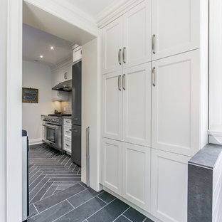Design ideas for a medium sized traditional galley kitchen pantry in Toronto with shaker cabinets, white cabinets, stainless steel appliances, quartz worktops, a breakfast bar, a submerged sink, grey splashback, ceramic splashback and slate flooring.