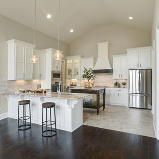 This is an example of a mid-sized transitional u-shaped eat-in kitchen in New Orleans with an undermount sink, recessed-panel cabinets, white cabinets, granite benchtops, beige splashback, stone tile splashback, stainless steel appliances, porcelain floors, multiple islands, beige floor and beige benchtop.