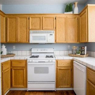 サンフランシスコの小さいトラディショナルスタイルのおしゃれなキッチン (ドロップインシンク、レイズドパネル扉のキャビネット、淡色木目調キャビネット、タイルカウンター、青いキッチンパネル、白い調理設備、ラミネートの床、アイランドなし) の写真