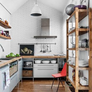 マドリードの中くらいのインダストリアルスタイルのおしゃれなキッチン (フラットパネル扉のキャビネット、無垢フローリング、アイランドなし、木材カウンター、グレーのキャビネット、白いキッチンパネル、サブウェイタイルのキッチンパネル、シルバーの調理設備) の写真