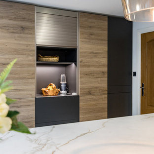 Inspiration for a large modern l-shaped open plan kitchen in Surrey with an integrated sink, flat-panel cabinets, grey cabinets, solid surface benchtops, white splashback, slate splashback, stainless steel appliances, porcelain floors, with island and grey floor.
