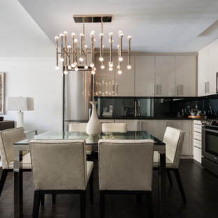 Design ideas for a small contemporary l-shaped open plan kitchen in Toronto with an undermount sink, flat-panel cabinets, grey cabinets, quartz benchtops, stainless steel appliances, dark hardwood floors, no island, black splashback and brown floor.