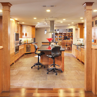 Large contemporary open concept kitchen photos - Example of a large trendy galley concrete floor open concept kitchen design in Sacramento with shaker cabinets, light wood cabinets, granite countertops, multicolored backsplash, mosaic tile backsplash, stainless steel appliances, an island and a farmhouse sink