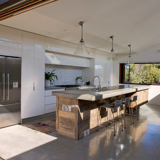 Photo of a large beach style galley open plan kitchen in Sydney with a drop-in sink, flat-panel cabinets, white cabinets, concrete benchtops, white splashback, subway tile splashback, stainless steel appliances, concrete floors, with island, grey floor and grey benchtop.