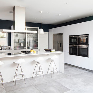 サセックスの大きいコンテンポラリースタイルのおしゃれなキッチン (ドロップインシンク、フラットパネル扉のキャビネット、白いキャビネット、ガラス板のキッチンパネル、白い調理設備、コンクリートの床、ラミネートカウンター、白いキッチンパネル) の写真