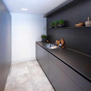 Design ideas for a small contemporary open plan kitchen in Cheshire with an integrated sink, flat-panel cabinets, black cabinets, laminate benchtops, black splashback, porcelain floors, no island, grey floor and black benchtop.