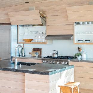 Foto de cocina rural con puertas de armario de madera clara, encimera de acero inoxidable, salpicadero blanco, salpicadero de vidrio templado, electrodomésticos de acero inoxidable, una isla y fregadero de un seno