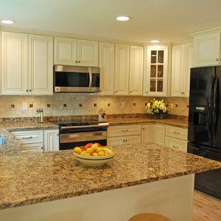 ボストンのトラディショナルスタイルのおしゃれなキッチン (アンダーカウンターシンク、レイズドパネル扉のキャビネット、ベージュのキャビネット、御影石カウンター、ベージュキッチンパネル、セラミックタイルのキッチンパネル、シルバーの調理設備、淡色無垢フローリング) の写真
