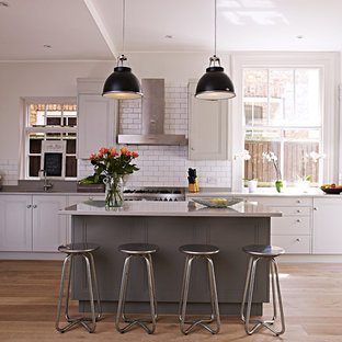 Inspiration for a large traditional kitchen/diner in London with recessed-panel cabinets, white cabinets, white splashback, metro tiled splashback, stainless steel appliances, light hardwood flooring and an island.